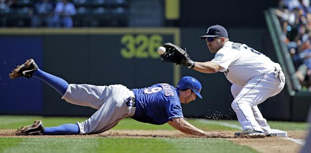 Texas Rangers' Adam Rosales (9) dives safely back to first base on a pickoff-attempt as Seattle Mariners first baseman Kendrys Morales, right, catches the ball in the second inning of a baseball game Wednesday, Aug. 27, 2014, in Seattle. AP Photo/Elaine Thompson)