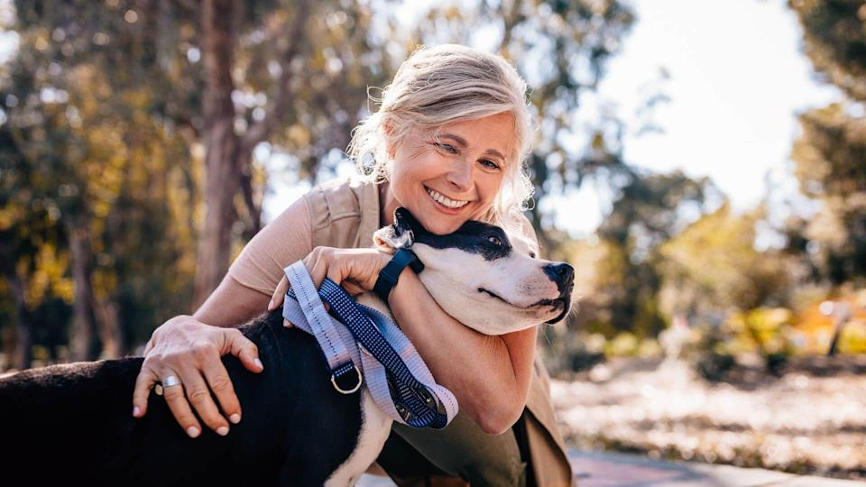Happy senior woman enjoying walk in nature and embracing pet dog in forest park.