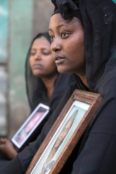 Zemed Derib, who lost family in the landslide, is pictured with a photograph of her mother, Yeshi, on March 18 2017, in Addis Ababa (AFP Photo/ZACHARIAS ABUBEKER)