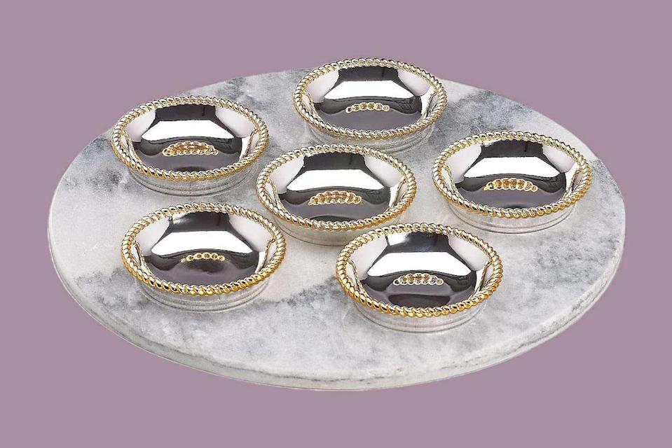 """<p>For real shine, this Seder plate features six nickel-plated bowls with roped gold rims. In its presentation, they all fit on a circular marble slate.</p> <p><em><strong>Shop Now:</strong></em> <em>Reed & Barton Roseland</em> <em>Seder Plate, $120.11, <a href=""""https://www.amazon.com/Reed-Barton-Roseland-Seder-Plate/dp/B06XRW8325?&linkCode=ll1&tag=mslpassoversederplatesrcoldiron0321-20&linkId=f963e5ae1ed0294b9ee37a9b95d7ca05&language=en_US&ref_=as_li_ss_tl"""" rel=""""sponsored noopener"""" target=""""_blank"""" data-ylk=""""slk:amazon.com"""" class=""""link rapid-noclick-resp"""">amazon.com</a>.</em></p>"""