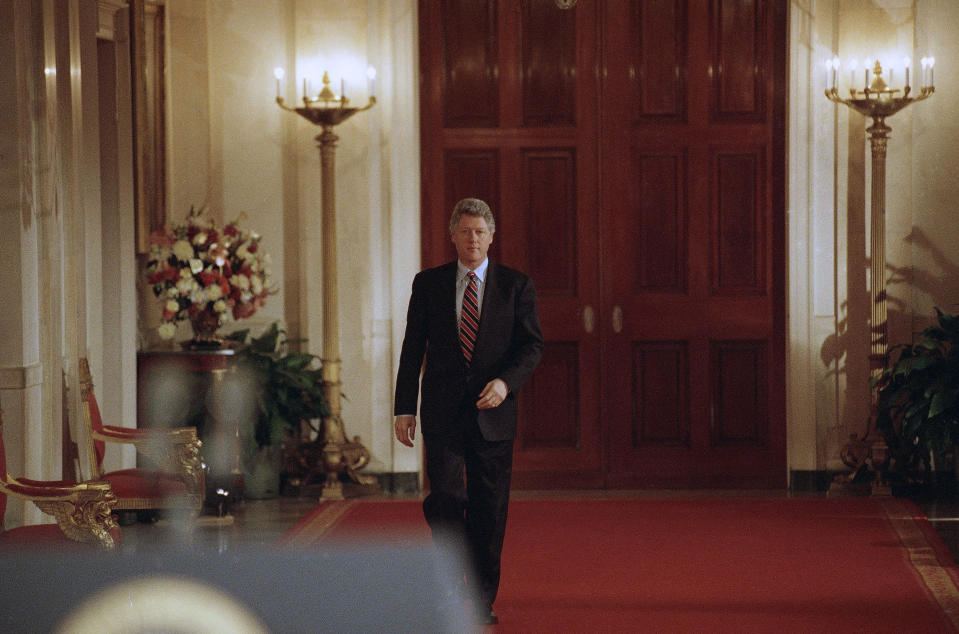 FILE - In this March 23, 1993, file photo, President Bill Clinton walks through the Grand Foyer to the East Room of the White House in Washington going to his first formal news conference. (AP Photo/Ron Edmonds, File)