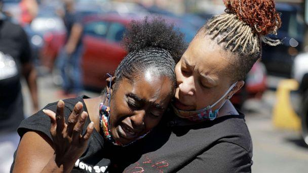 PHOTO: Two women pray, June 2, 2020, in Louisville, Ky., near the intersection where David McAtee was killed Sunday evening. (Darron Cummings/AP)