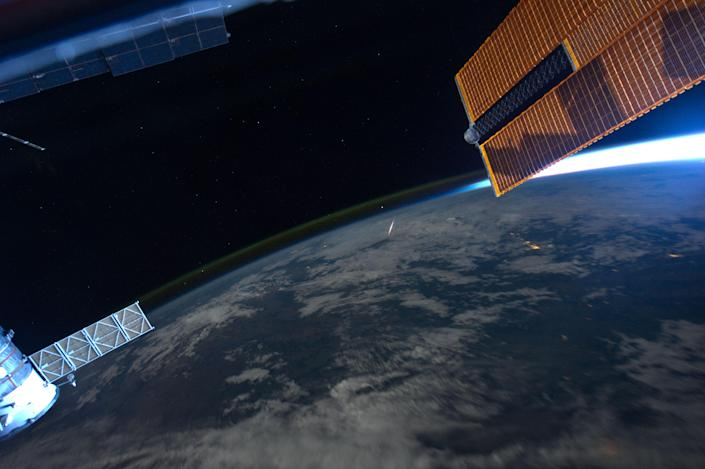 """Astronaut Ron Garan, Expedition 28 flight engineer, tweeted this image from the International Space Station on Aug. 14 with the following caption: """"What a 'Shooting Star' looks like from space, taken yesterday during Perseid Meteor Shower."""" The image was photographed from the orbiting complex on Aug. 13 when it was over an area of China approximately 400 kilometers to the northwest of Beijing. The rare photo opportunity came as no surprise since the Perseid Meteor Shower occurs every year in August. The meteors are particles that originate from the comet Swift-Tuttle along its orbital path; the comet's orbit is close enough for these particles to be swept up by the Earth's gravitational field each year. Green and dim yellow airglow appears as thin layers visible above the limb of the Earth, extending from image left to upper image right. Atoms and molecules above 50 kilometers in the atmosphere are excited by sunlight during the day, and then release this energy at night producing primarily green light observable from orbit. The sun is low on the horizon as it appears near part of one of the station's solar panel arrays at image upper right. (Photo: NASA/Ron Garan)"""