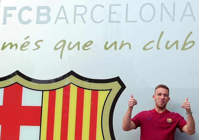 Brazilian soccer player Arthur Melo poses in front of a FC Barcelona logo at their offices next to Camp Nou stadium in Barcelona, Spain July 11, 2018. REUTERS/Albert Gea
