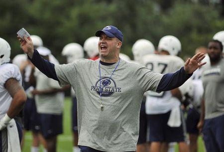 Penn State football coach Bill O'Brien yells at members of the media to put away their cameras during a team practice in State College, Pennsylvania August 9, 2012. REUTERS/Pat Little