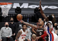 Portland Trail Blazers guard Damian Lillard (0) drives to the basket on Detroit Pistons forward Sekou Doumbouya, right, during the first half of an NBA basketball game in Portland, Ore., Saturday, April 10, 2021. (AP Photo/Steve Dykes)