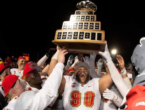 University of Calgary Dinos' J-Min Pelley raises the Vanier Cup in 2019. CBC Sports announced a multi-year partnership with U Sports on Monday to broadcast national championships, including the men's football title game. (Jacques Boissinot/The Canadian Press - image credit)
