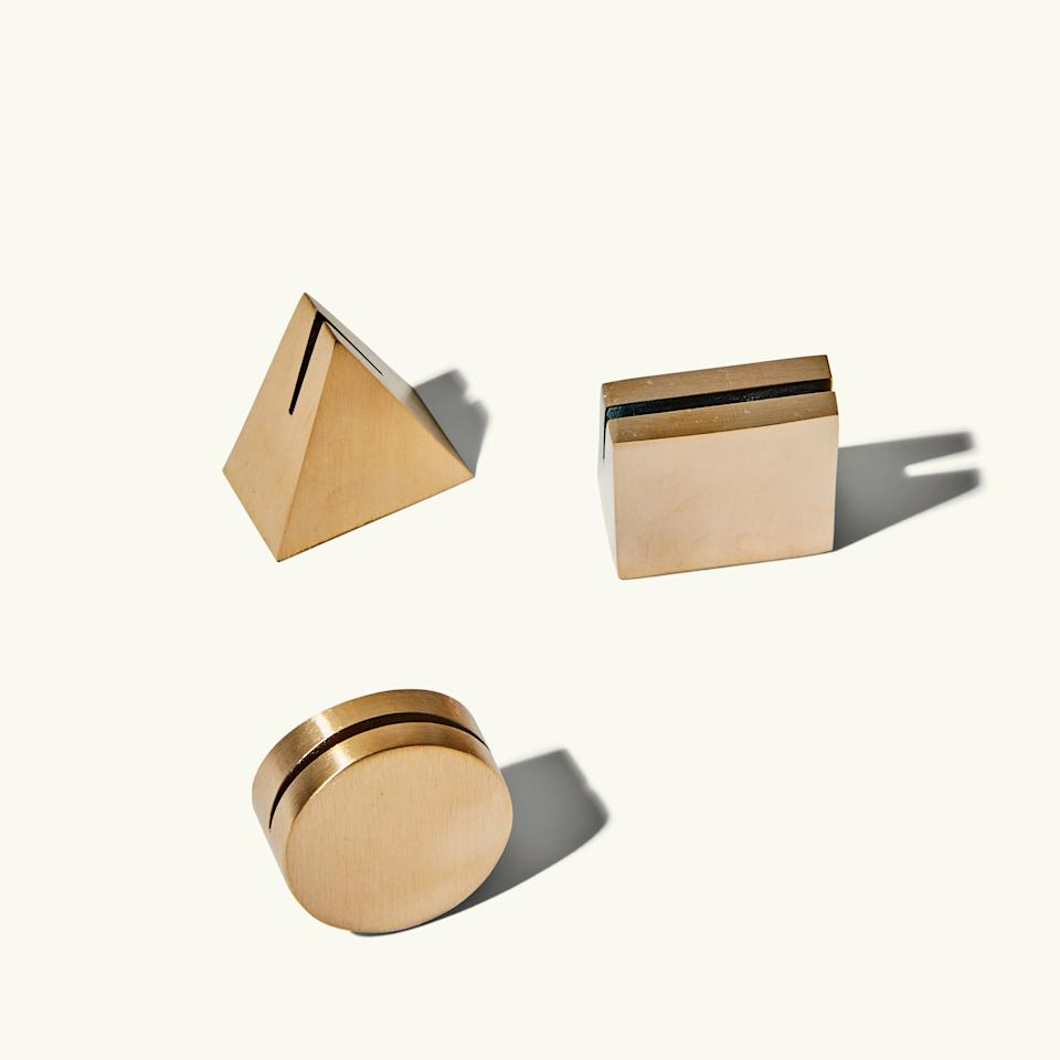 """Trying to avoid a repeat of last year's Great Canned Cranberry Sauce Debate? Deploy these solid brass place card holders to gingerly enforce a seating chart—or display treasured family photos with a metallic twinkle.<em>Buy it:</em> <a href=""""https://yielddesign.co/products/geo-stands-set-of-3"""" rel=""""nofollow"""" target=""""_blank""""><em>Geo Stands, $88 for set of three; yielddesign.co</em></a>"""