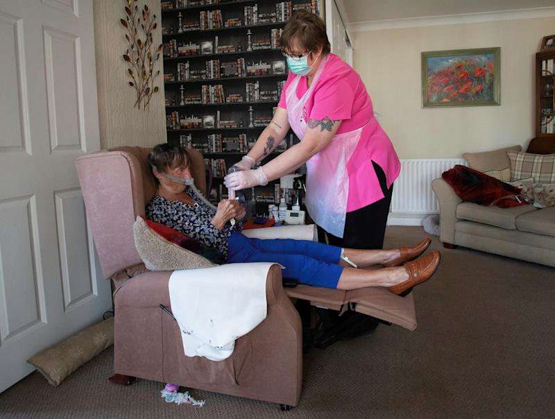 Dawn, a support staff member from Elite Care wears PPE (personal protective equipment) as she tends to her client Tina during a home visit in Scunthorpe, northern England on May 8, 2020. - Tina has multiple complex needs as she suffers with Multiple Sclerosis and is considered in the high risk category during the current COVID-19 pandemic. Home support staff members are an essential key worker service to those with disabilities stranded at home under the lockdown, providing specialist care and human kindness. Dawn has worked with Tina for seven years and although Tina's disabilities limit her outdoor recreation, she misses most of all hers and Dawn's visits to the local park for their weekly latte drink. (Photo by Lindsey Parnaby / AFP) (Photo by LINDSEY PARNABY/AFP via Getty Images)