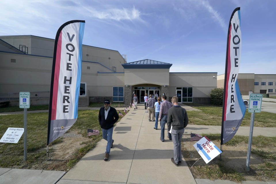 People wait to cast their ballot on the first day of early voting at an advance polling location Saturday, Oct. 17, 2020, in Overland Park, Kan. (AP Photo/Charlie Riedel)