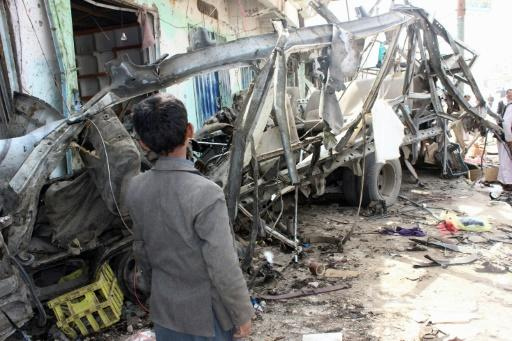 A Yemeni child stands next to the destroyed bus