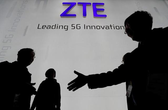FILE PHOTO - Visitors pass in front of the ZTE booth at the Mobile World Congress in Barcelona