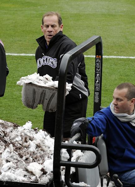Colorado Rockies owner Dick Monfort shovels snow from the field before the start of a baseball double-header between the New York Mets and the Colorado Rockies on Tuesday, April 16, 2013, in Denver. (AP Photo/Jack Dempsey)
