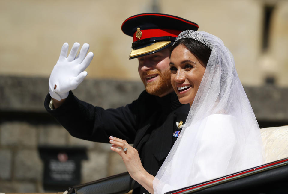 The royal couple wave to the crowds from their horse-drawn carriage (Picture: PA)