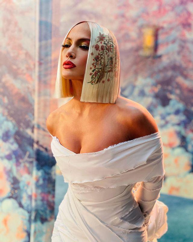 """<p>Giving us serious hair envy once again, J Lo rocked a super blunt bleached blonde bob adorned with a delicate floral hair stencil courtesy of her go-to hairstylist Chris Appleton.</p><p><a href=""""https://www.instagram.com/p/CJOiSQIhBH8/?utm_source=ig_embed&utm_campaign=loading"""" rel=""""nofollow noopener"""" target=""""_blank"""" data-ylk=""""slk:See the original post on Instagram"""" class=""""link rapid-noclick-resp"""">See the original post on Instagram</a></p>"""