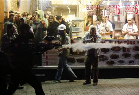 Customers and cooks inside a kebab shop watch as a riot police officer fires plastic paintball gun pellets to disperse demonstrators during an anti-government protest in central Istanbul December 27, 2013. REUTERS/Murad Sezer