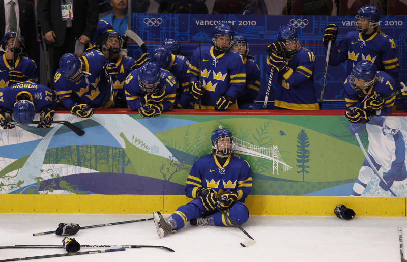 Sweden's hockey team watch as Finland players celebrate their win in overtime in their women's ice hockey bronze medal game at the Vancouver 2010 Winter Olympics February 25, 2010. REUTERS/Shaun Best (CANADA)