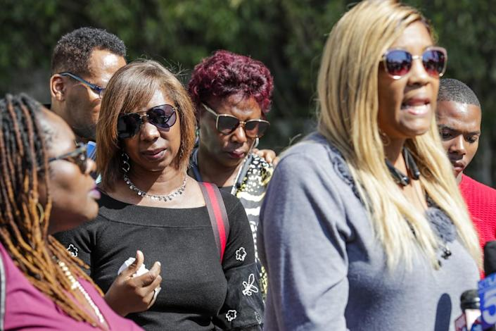 LaTisha Nixon, the mother of Gemmel Moore, with relatives of Timothy Dean.