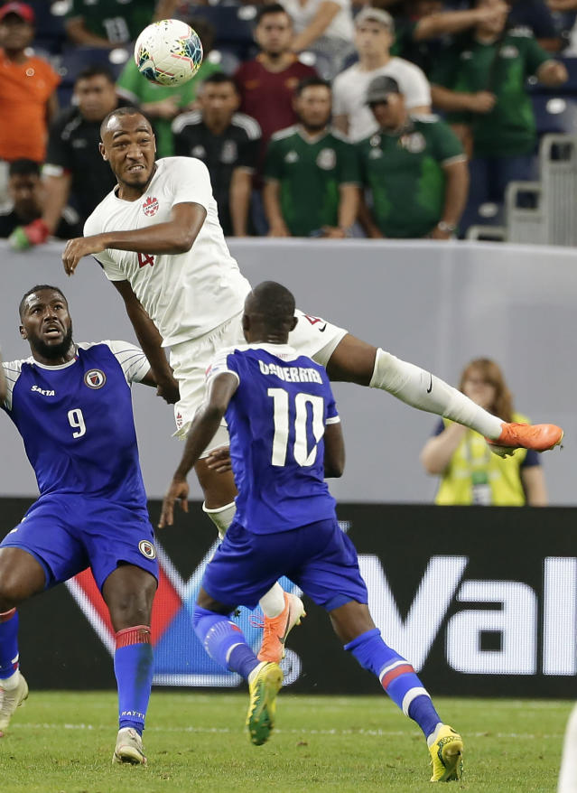 Canada defender Derek Cornelius (4) jumps for a header between Haiti forward Duckens Nazon (9) and midfielder Wilde-Donald Guerrier (10) during the second half of a CONCACAF Gold Cup quarterfinal soccer match Saturday, June 29, 2019, in Houston. (AP Photo/Michael Wyke)