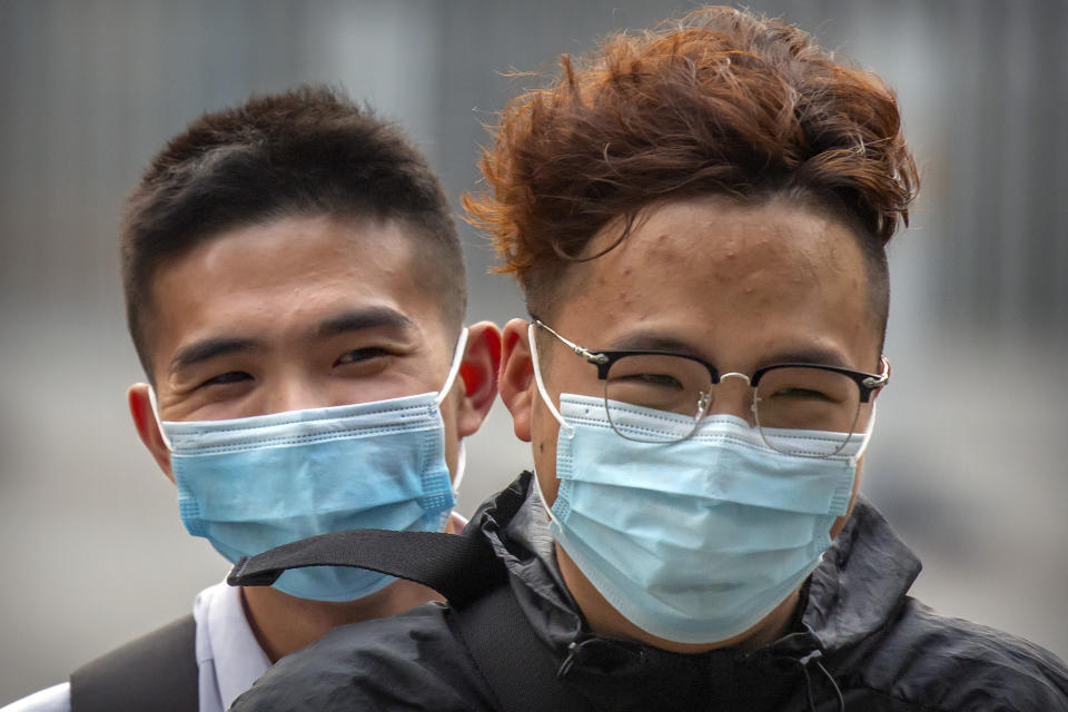 People wearing face masks to protect against the coronavirus ride a motor scooter in Beijing, Wednesday, July 29, 2020. China reported more than 100 new cases of COVID-19 on Wednesday as the country continues to battle an outbreak in Xinjiang. (AP Photo/Mark Schiefelbein)