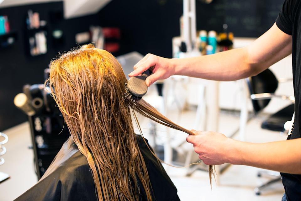 Hairdresser is brushing hair of young woman