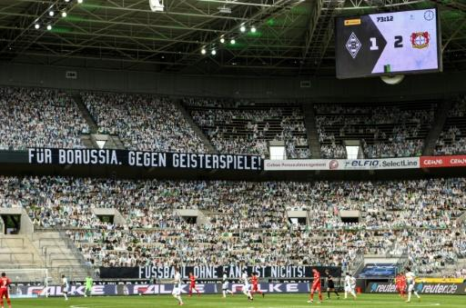 "Cardboard cut-outs of fans and a banner reading ""For Borussia, against matches behind locked doors"" during Saturday's 3-1 defeat at home to Bayer Leverkusen"