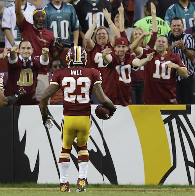 Washington Redskins fans greet cornerback DeAngelo Hall in the end zone after he scored on an interception during the first half of an NFL football game against the Philadelphia Eagles in Landover, Md., Monday, Sept. 9, 2013. (AP Photo/Alex Brandon)