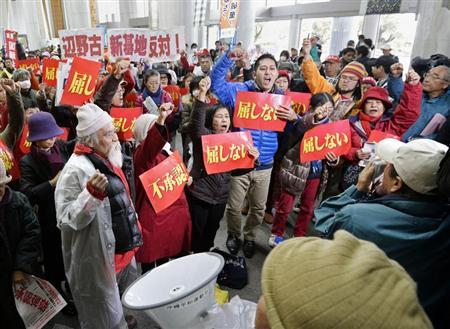 Protesters holding banners raise their fists as they shout slogans during a rally against the relocation of a U.S. military base, at the entrance of the Okinawa prefectural government office building, in Naha on the Japanese southern islands of Okinawa, in this photo taken by Kyodo December 27, 2013. REUTERS/Kyodo