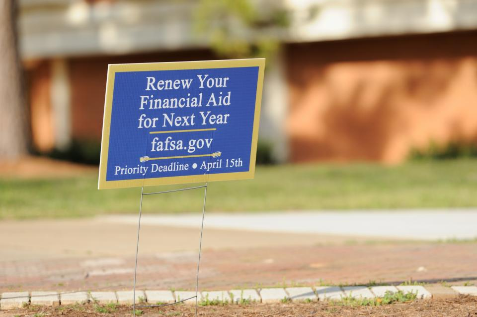 Americus, Georgia, USA - March 13, 2016:  Yard sign encouraging students to renew financial aid for next year, with the web site fafsa.gov.  Priority deadline of April 15th.  Sign placed on campus of Georgia Southwestern State University campus, a public university in Americas, Georgia, near the library.
