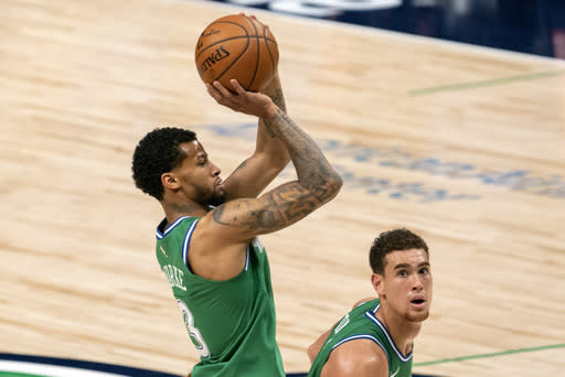 Dallas Mavericks guard Trey Burke (3) shoots a three-point basket as center Dwight Powell looks on during the second half of an NBA basketball game against the Orlando Magic, Saturday, Jan. 9, 2021, in Dallas. (AP Photo/Jeffrey McWhorter)