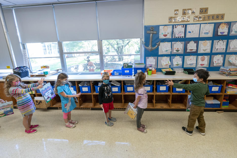 Kindergarten students check to make sure they are standing at the proper social distancing space as they line up to go outside during the coronavirus outbreak at the Osborn School, Tuesday, Oct. 6, 2020, in Rye, N.Y. (AP Photo/Mary Altaffer)