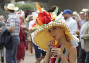 FILE - In this May 4, 2019, file photo, a woman wears a colorful hat at Churchill Downs before the 145th running of the Kentucky Derby horse race in Louisville, Ky. Next months Kentucky Derby will run without fans at Churchill Downs. The historic track cited rises in COVID-19 cases in the Louisville area. (AP Photo/Charlie Riedel, File)