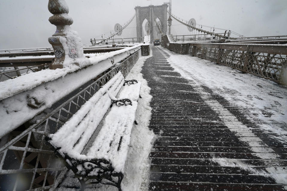 A snowplow makes clears the slippery wooden pedestrian walkway on the Brooklyn Bridge during the second snowstorm to hit the New York area and the Northeast in less than a week, Sunday, Feb. 7, 2021, in the Brooklyn borough of New York. (AP Photo/Kathy Willens)