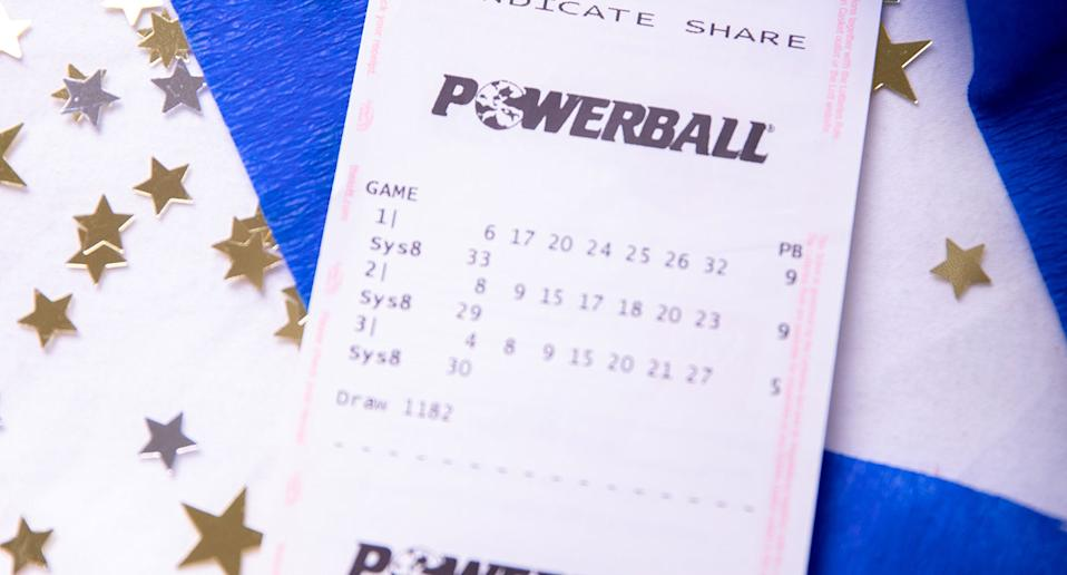 A powerball ticket sits on a table surrounded by streamers and confetti. Source: The Lott