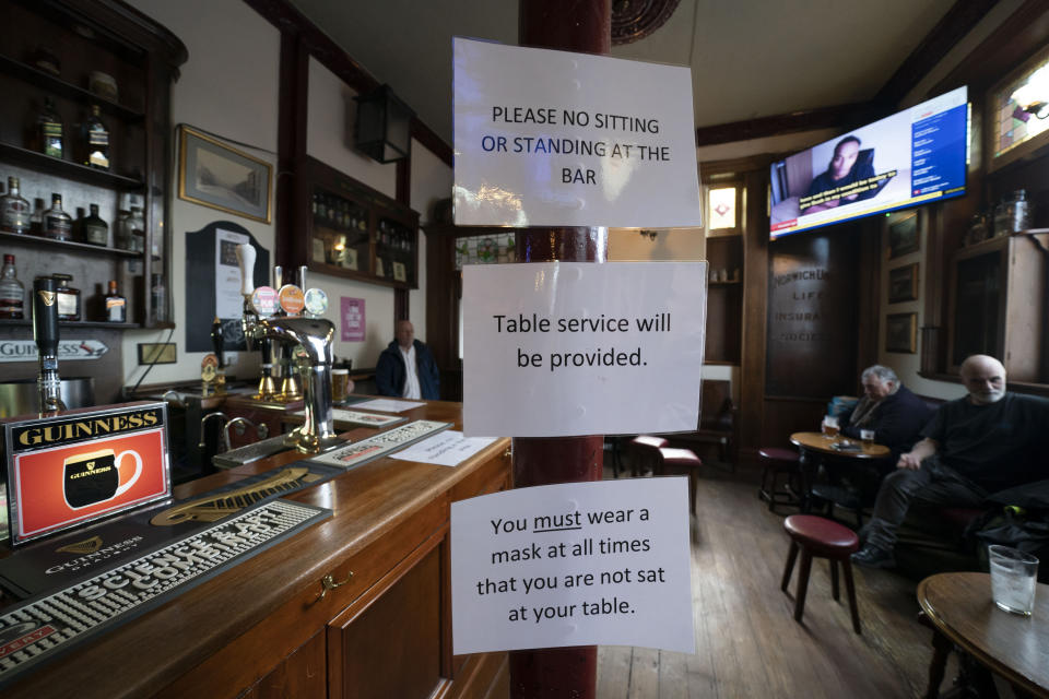 FILE - In this Oct. 12, 2020 file photo, signs showing anti-coronavirus guidance measures are displayed in the Dispensary pub in Liverpool, England. Hundreds of thousands of jobs in Britain hang in the balance as employers try to plot their way through a resurgence of the coronavirus without the backstop of a national salary support program. (AP Photo/Jon Super, file)