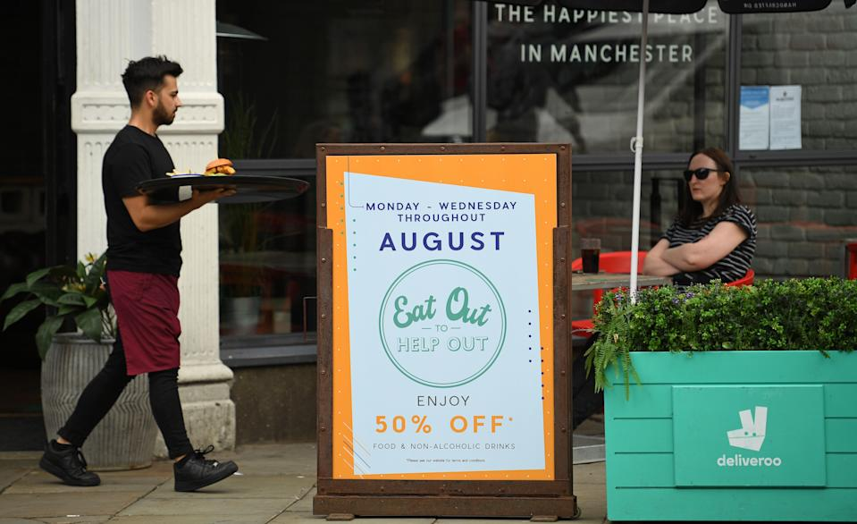 """A server carries food past a sign promoting the British Government's """"Eat out to Help out"""" COVID-19 scheme to get consumers spending again, outside a restaurant in Manchester, northwest England on August 3, 2020. - Britain's """"Eat out to Help out"""" scheme began Monday, introduced last month by Chancellor Rishi Sunak to help boost the economy claw its way from a historic decline sparked by the coronavirus crisis. (Photo by Oli SCARFF / AFP) (Photo by OLI SCARFF/AFP via Getty Images)"""