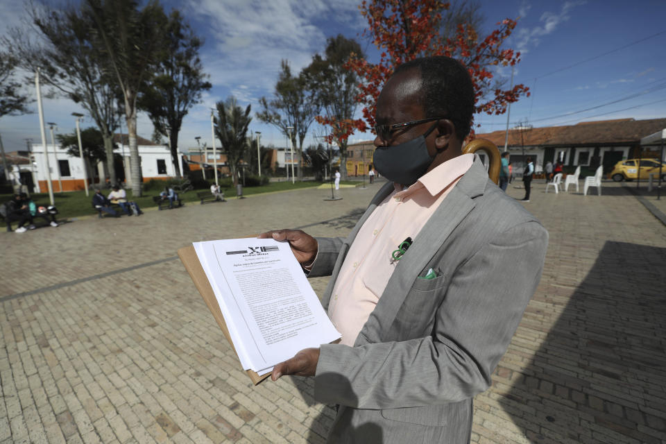 Community leader Baldoino Asprilla shows a death threat that was sent to him, during an interview in Bogota, Colombia, Thursday, Dec. 17, 2020. Last year 120 community leaders were murdered in Colombia according to the U.N.'s High Commissioner for Human Rights, up from 107 a year earlier. (AP Photo/Fernando Vergara)