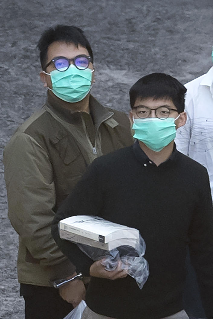 Hong Kong activists Joshua Wong, right, and Ivan Lam, left, are escorted by Correctional Services officers for a prison van before appearing in a court, in Hong Kong, Wednesday, Dec. 2, 2020. Prominent Hong Kong pro-democracy activist Wong and two other activists, Lam and Agnes Chow, were taken into custody after they pleaded guilty to charges related to a demonstration outside police headquarters during anti-government protests last year. (AP Photo/Kin Cheung)