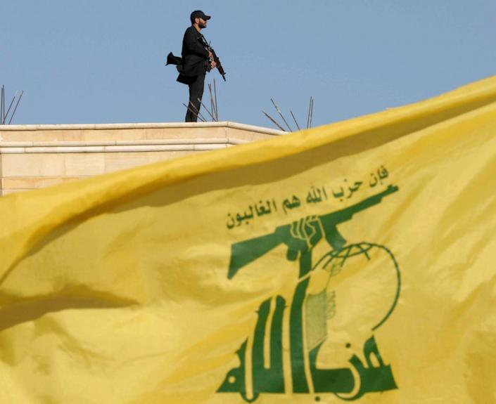 A Hezbollah member carries his weapon on top of a building as Lebanon's Hezbollah leader Sayyed Hassan Nasrallah appears on a screen during a live broadcast to speak to his supporters at an event marking Resistance and Liberation Day, in Bekaa valley May 25, 2016. The event is to commemorate the 16th anniversary of Israel's withdrawal from southern Lebanon. REUTERS/Hassan Abdallah