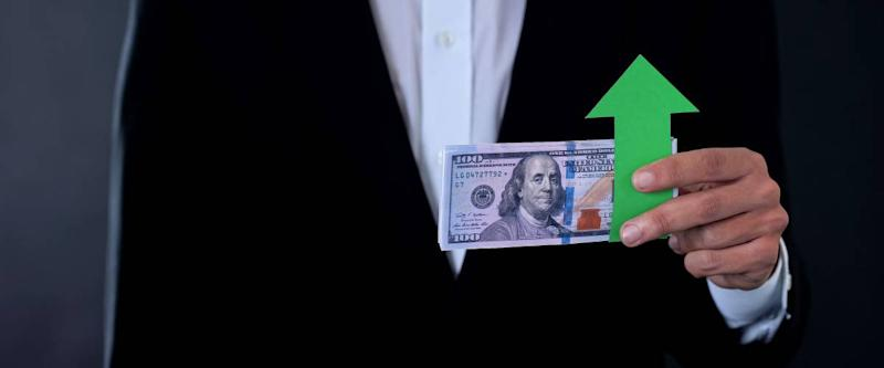 man holding banknote, arrow pointing up indicating strong dollar and strong US economy
