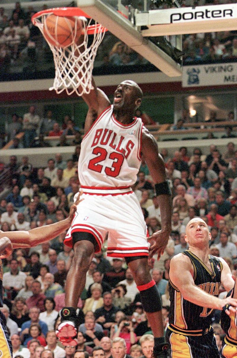 Chicago Bulls Michael Jordan stuffs the net for two during Game One of the Eastern Conference Finals against the Indiana Pacers Sunday, May 17, 1998, in Chicago. Pacers Chris Mullin, right, looks on (AP Photo/Beth A. Keiser)
