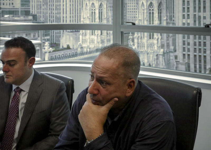 In this Tuesday, Oct. 29, 2019, photo, Ramon Mercado, right, recalls childhood clergy sexual abuse while his lawyer, Adam Slater, left, takes notes during an interview in his office overlooking St. Patrick's Cathedral, in New York. Mercado said he kept silent about the abuse he suffered at the hands of a New York priest, in part not to upset his devout Catholic mother. (AP Photo/Bebeto Matthews)