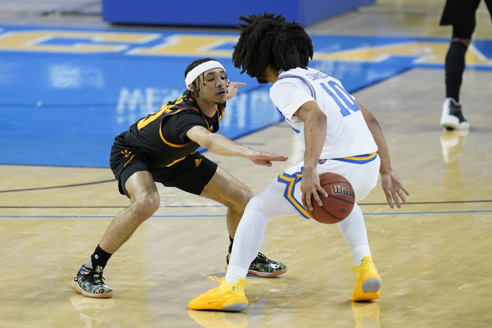Arizona State guard Jaelen House (10) defends against UCLA guard Tyger Campbell (10) during the first half of an NCAA college basketball game Saturday, Feb. 20, 2021, in Los Angeles. (AP Photo/Ashley Landis)