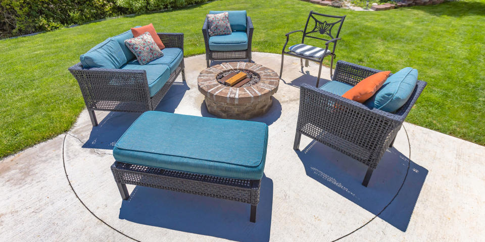 Circular fire pit and chairs on a sunny backyard. A circular stone fire pit surrounded by chairs with blue cushions and pillows. The fire pit is on a backyard patio with landscaped ground.