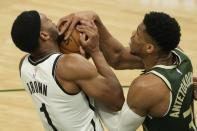 Brooklyn Nets' Bruce Brown and Milwaukee Bucks' Giannis Antetokounmpo battle for the ball during the first half of Game 3 of the NBA Eastern Conference basketball semifinals game Thursday, June 10, 2021, in Milwaukee. (AP Photo/Morry Gash)