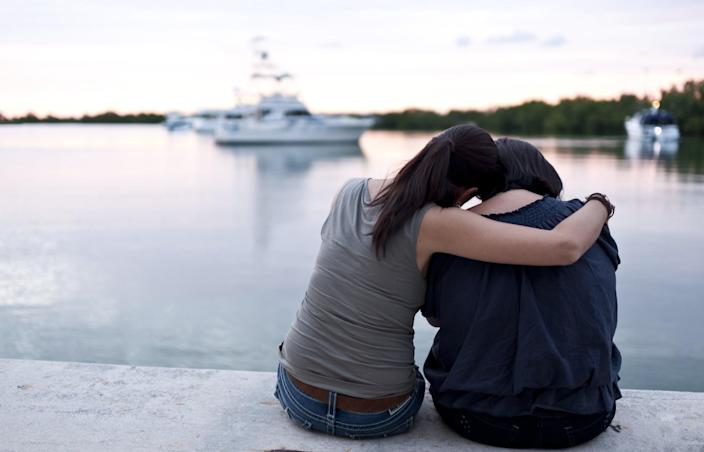 Two mature hispanic women sitting at the docks embracing from behind