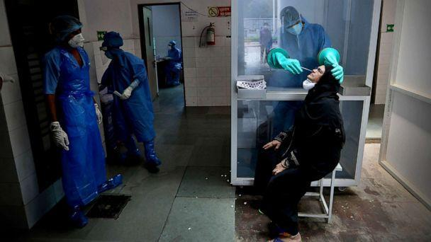 PHOTO: A health worker takes a nasal swab of a woman for COVID-19 test at a hospital in New Delhi, India, July 6, 2020. (Manish Swarup/AP)