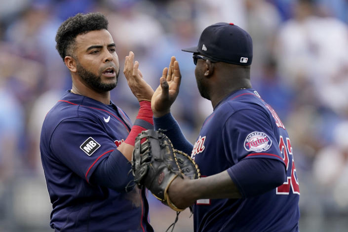Minnesota Twins' Nelson Cruz, left, and Miguel Sano celebrate after their baseball game against the Kansas City Royals Saturday, June 5, 2021, in Kansas City, Mo. The Twins won 5-4. (AP Photo/Charlie Riedel)