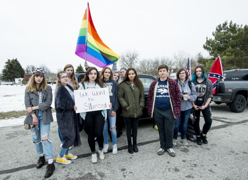 """Counter-protesters display rainbow flags and signs as a caravan of Confederate-flag-bearing trucks park along the outer drive of Bay City Western High School in Auburn, Mich., Wednesday, April 18, 2018. """"We have such a small minority population of students and we're in a conservative area"""" said Kendrix Szilagyi, pictured at center left with a sign. """"If they went to Saginaw or Bay City Central they wouldn't let this happen""""(Jacob Hamilton/The Bay City Times via AP)"""