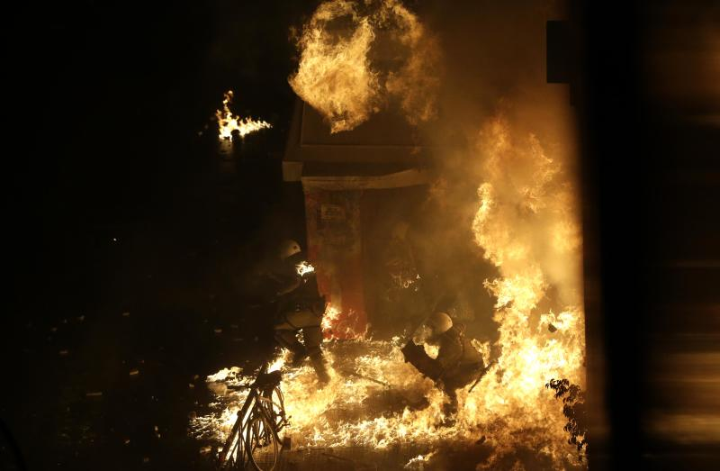 A riot police officer is engulfed by petrol bomb flames thrown by protesters in front of the parliament during clashes in Athens, Wednesday Nov. 7, 2012. Greece's fragile coalition government faces its toughest test so far when lawmakers vote later Wednesday on new painful austerity measures demanded to keep the country afloat, on the second day of a nationwide general strike. The 13.5 billion euro ($17.3 billion) package is expected to scrape through Parliament, following a hasty one-day debate. But potential defections could severely weaken the conservative-led coalition formed in June with the intention of keeping Greece in the euro. (AP Photo/Dimitri Messinis)